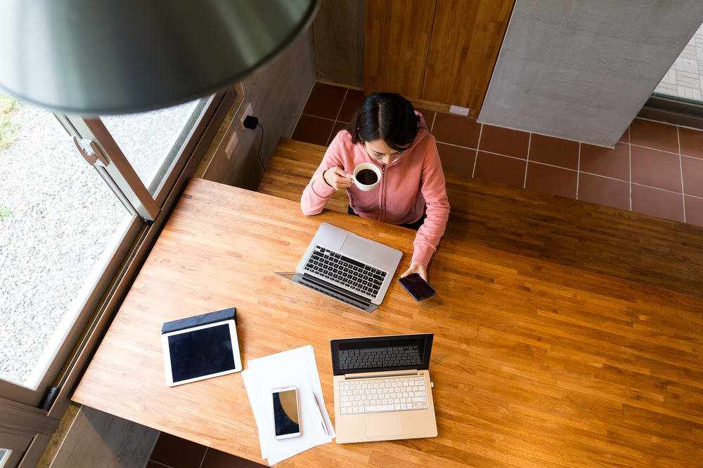 Top view of woman drinking of coffee with checking the message on cellphone